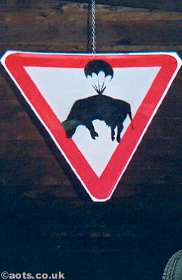 Banksy - modified sign depicting a cow and a parachute at Turf War